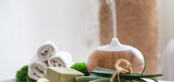 Spa composition with the aroma of a modern oil diffuser with body care products . Twisted white towels, and aloe Vera . The concept of Wellness for body and health .
