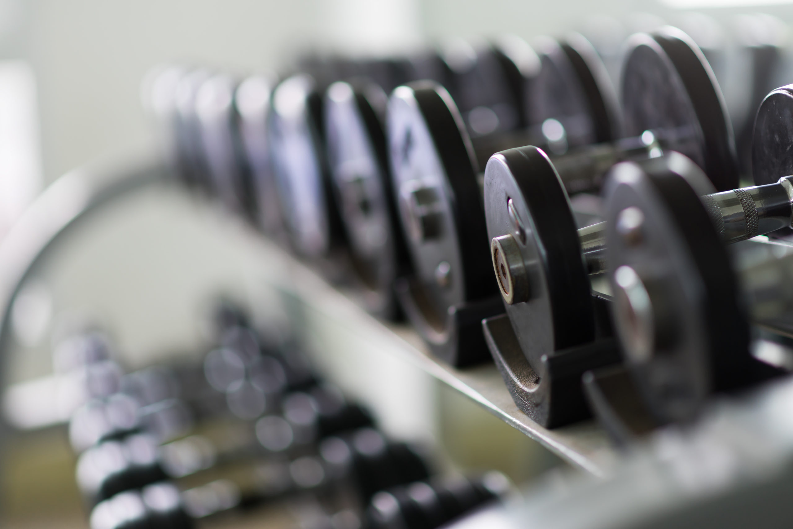 Rows of metal dumbbells on rack in the gym / sport club. Weight Training Equipment.